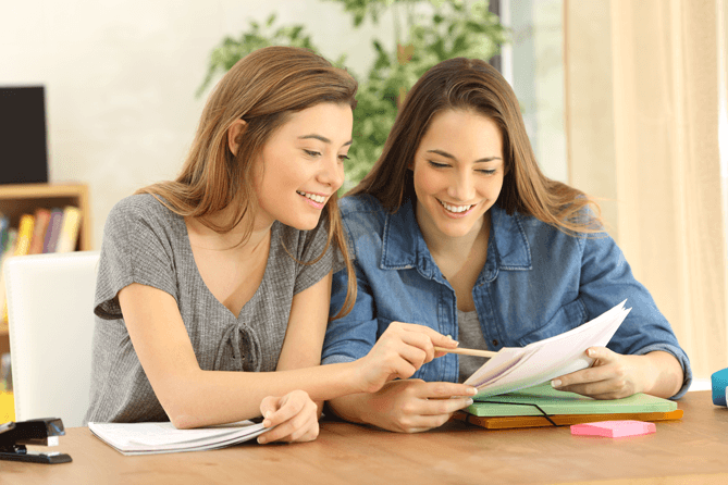 High school student with woman reading documents and smiling.